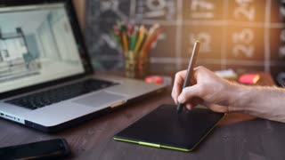 Creative businessman writing on graphic tablet while using laptop in office