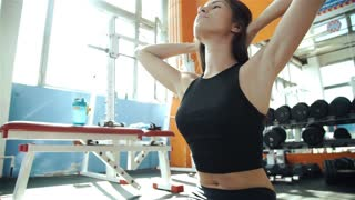 Cute Sporty young woman doing exercise in a fitness center with her personal coach. She is working exercises to strengthen her chest 20s. 1080p Slow Motion