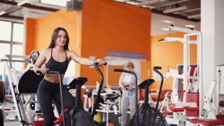 Female on gym bike doing cardio exercise.