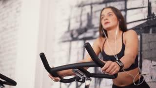 Female on gym bike doing cardio exercise.