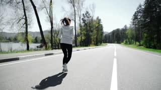 Female runner jogging on mountain road training for marathon.