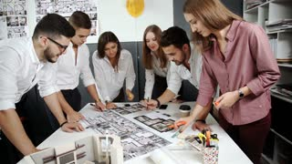Four architects standing and planning around a table while looking down at blueprint 20s 4k.
