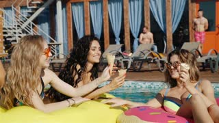 friends eating ice cream in a swimming pool. 20s. 1080p Slow Motion.