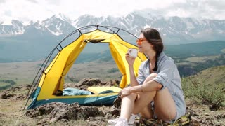 Girl near bonfire. Travel, tourism, camping - young slim sporty woman tourist brunette at the beautiful nature landscape sitting near the tent by the fire. Girl with drink in mug in her hands