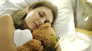 Girl sleeps in a bed with a toy a teddy bear 4k 20s