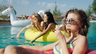 girls sitting outdoors eating ice creams next to pool on a summer day in a backyard. 20s. 1080p Slow Motion.