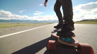 Guy on his longboard skate. Close up of longboard and foot. Side view. Tracking shot