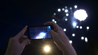 hands of man taking the photo to fireworks with the new smartphone