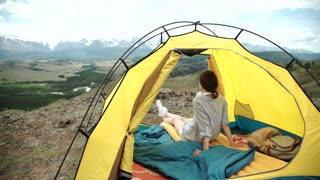 Happy woman sitting in a tent ,view of mountains