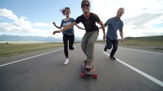 Happy young couple having fun with skateboard on the road. Young man and woman skating together on a sunny day