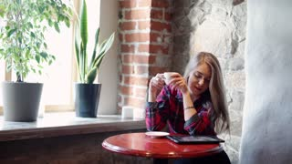 Happy young woman drinking coffee and using  tablet computer in a coffee shop