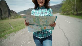 Happy young woman holding map on road