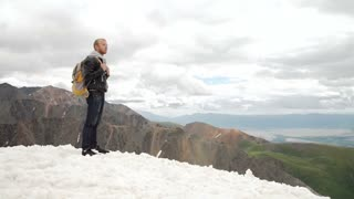 Hiker looking at view in high altitude mountain above the clouds.