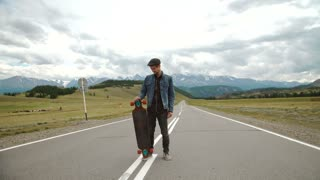 man carries a longboard. The boy goes on the asphalted road holding a longboard