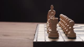 man playing wooden chess pieces