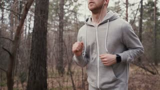 Man running in forest woods training and look at smart watches.