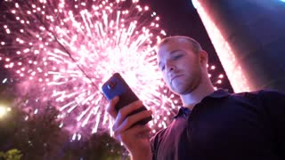 man use smart phone , image of firework as a background.