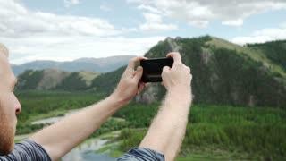 Man using smart phone take a photo mountain view