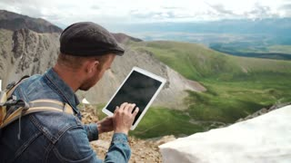 man's hands touching screen of digital tablet on the background of mountains