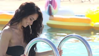 Portrait of attractive young woman going out from swimming pool outdoors. 20s. 4k Slow Motion