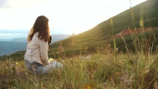 Portrait of woman with backpacker sitting on top of the mountain and enjoying sunset and valley view. 
