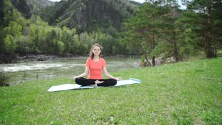 Practicing yoga in the morning, mountains and sun ray in the background.