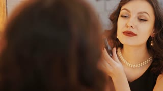 Reflection of young beautiful woman applying her make-up, looking in a mirror
