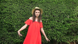 SLOW MOTION. Beautiful happy model standing playful in red dress on nature