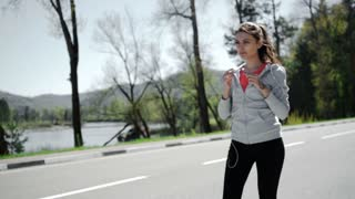 SLOW MOTION portrait of a young woman jogging and listening to the player