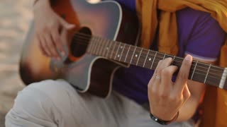 SLOW MOTION. young boy plays guitar at sunset