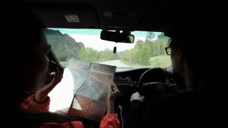 slowmotion. Rear view shot of a young couple on road trip reading a map