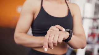 Smart watch showing a heart rate of exercising woman in gym