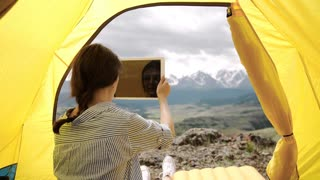 Tablet pc - camping woman taking picture photo selfie selfportrait at campsite in.