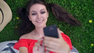 Top view photo of beautiful young woman lying on green grass.