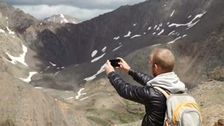 Tourist takes photos with smart phone on peak of rock