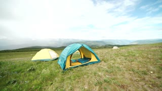 Tourist tent in camp among meadow in the mountain
