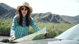 Travel - young woman with car look at road map on a beach against sea and sky
