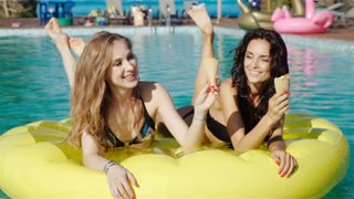 two girls of swimsuit floating in the pool float. 20s. 1080p Slow Motion