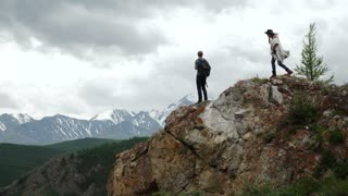 Two people standing on top of a mountain