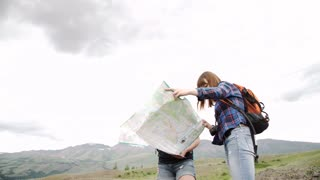 two woman wanderers exploring map while sitting on a mountain hill in sunny summer day during their weekend,two travelers searching road on atlas while taking break after hiking in the countryside.