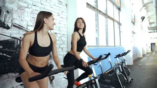 Two women talking while training in a spinning class in gym, 20s. 1080p Slow Motion