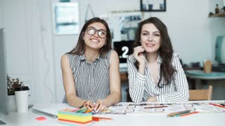 Two women working together at an architect office. look at camera