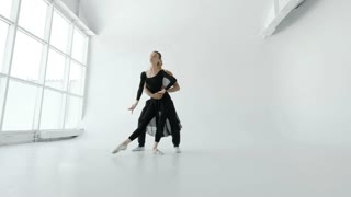 20s Female in black dress and male black sports pants dancers warm up before the performance in a white room with a large window 4k.