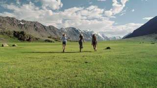 20s Three girlfriends running free on green grass meadow sunny day and background of mountain - Friendship girls and freedom concept with young happy women moving free at camping experience tossing