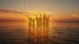 A group of five young teenager friends travel to the beach looking at the sea