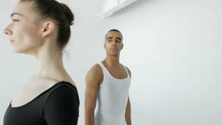 A young ballet dancer in white and a attractive 20s ballerina in black dress raises an attractive ballerina in her arms, close-up at the beginning of the video, then the camera moves away 4k.