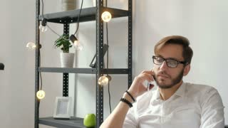 Attractive european guy talking on phone while using laptop at workplace 20s 4k