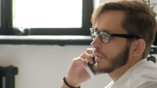 Attractive european guy talking on phone while using laptop at workplace 20s 4k.