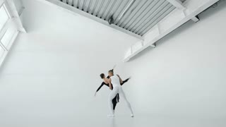 Attractivw 20s girl in white and a guy in black ballet dancers beautifully dance in white ballet class 1080p slow motion