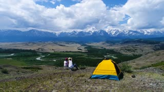 Back view of couple tourists covered with a plaid sitting on a hill near the tent and looking into the distance over the mountains, aerial slow motion 4k